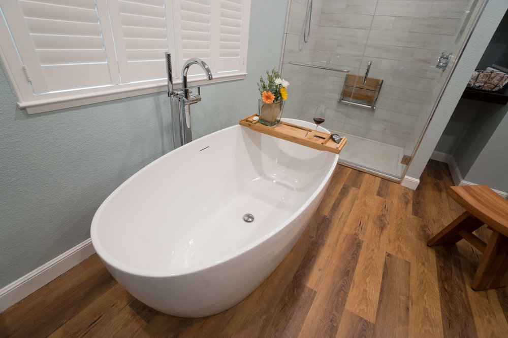 Spa tub with freestanding faucet and handheld shower. Custom shutters complete the clean, uncluttered look.