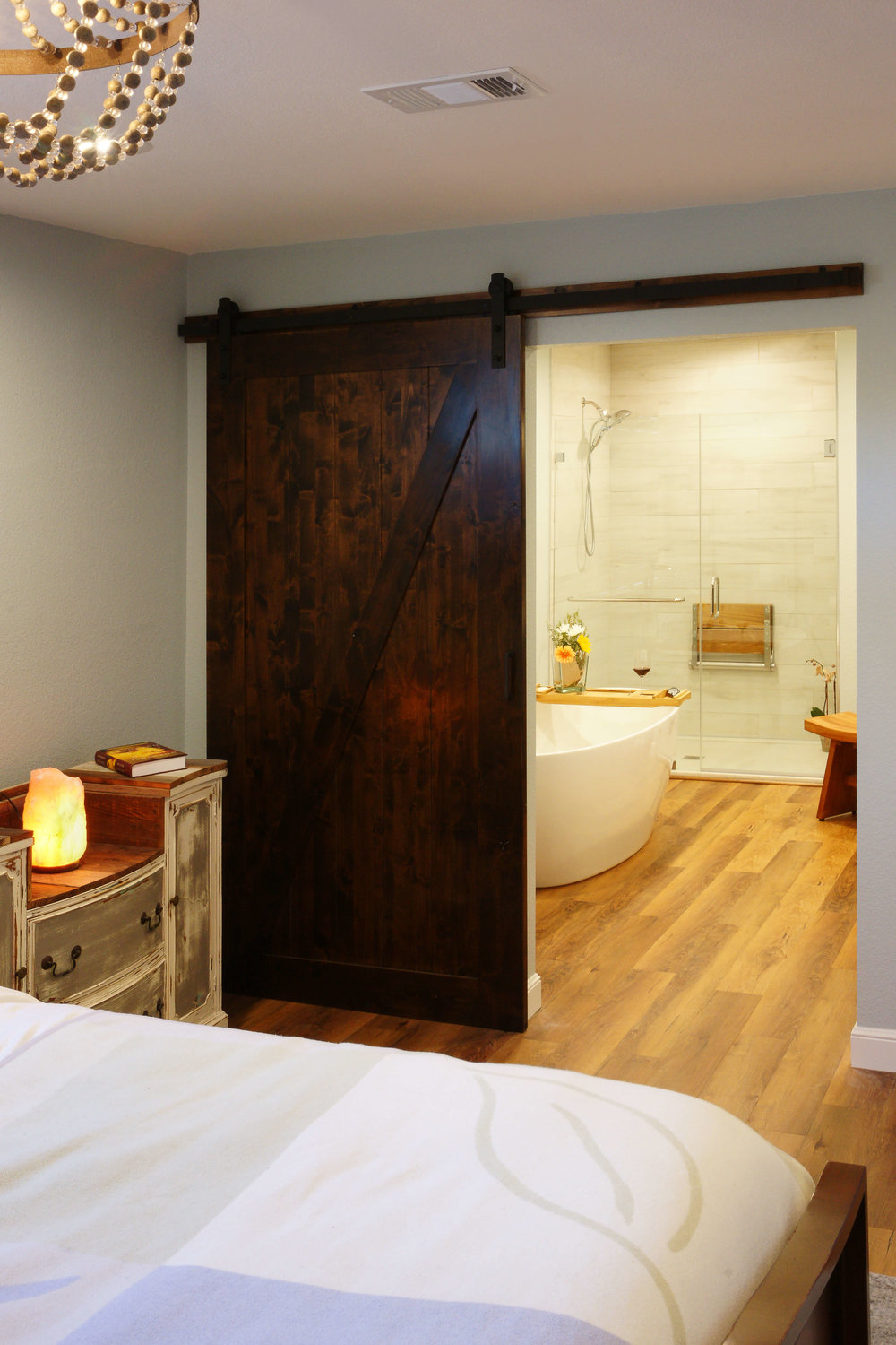Design detail: Sliding barn door continues the reclaimed feel and maximizes space