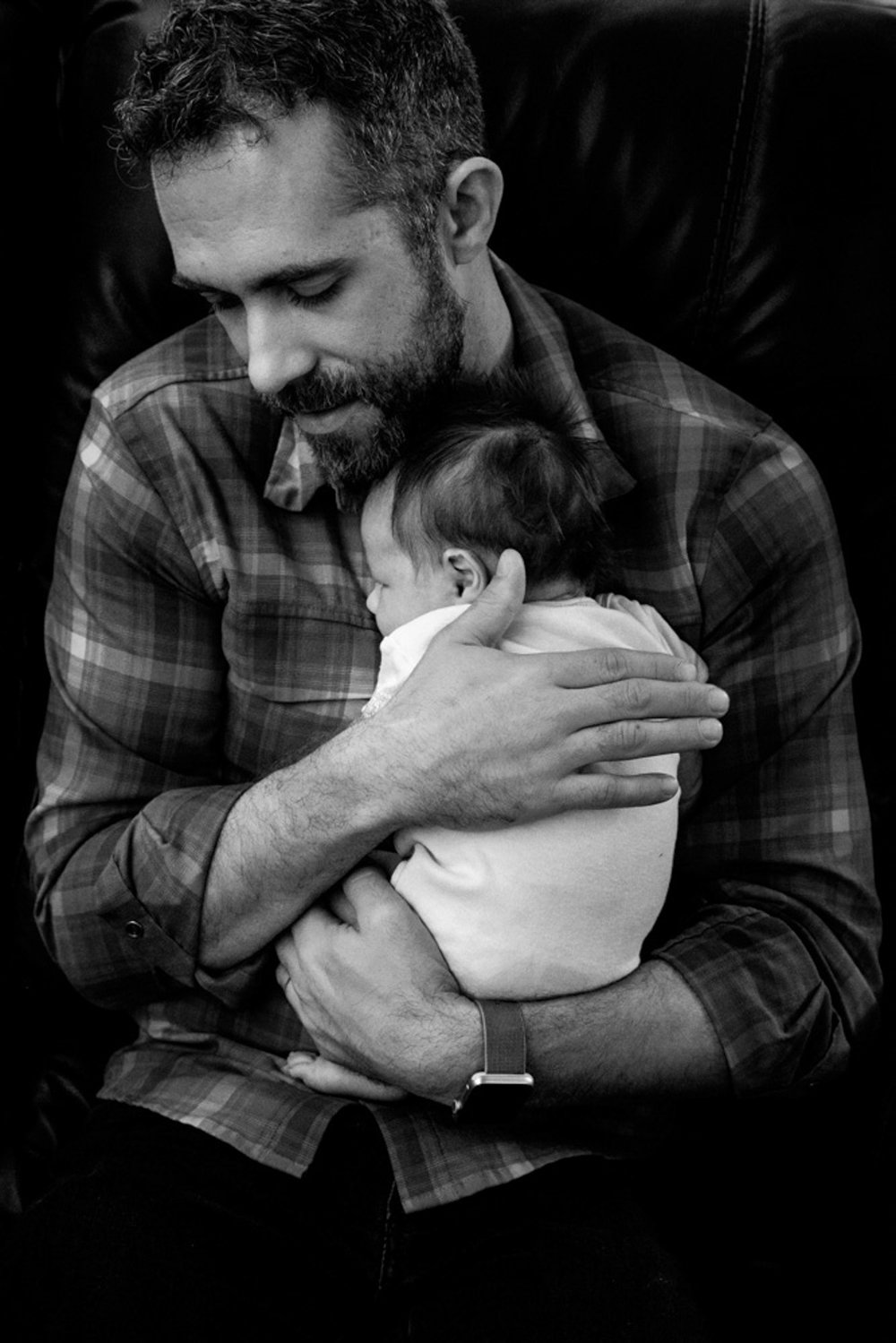 dad seated and snuggling newborn baby in black and white