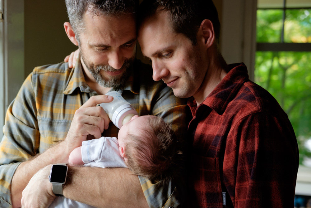 two dads snuggling a newborn with a bottle
