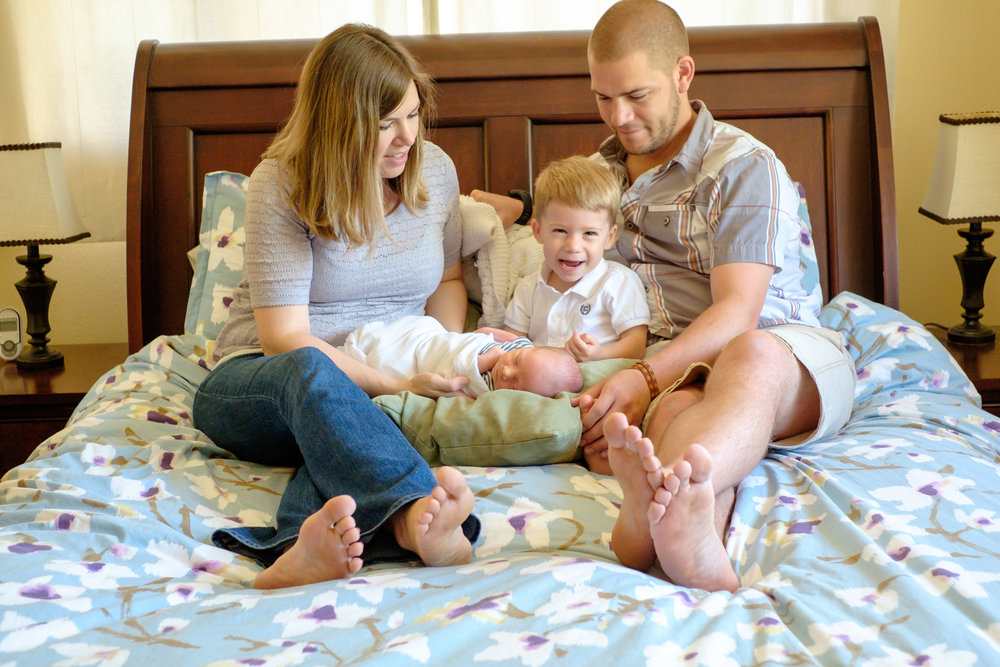 family snuggling on bed with toddler and new baby