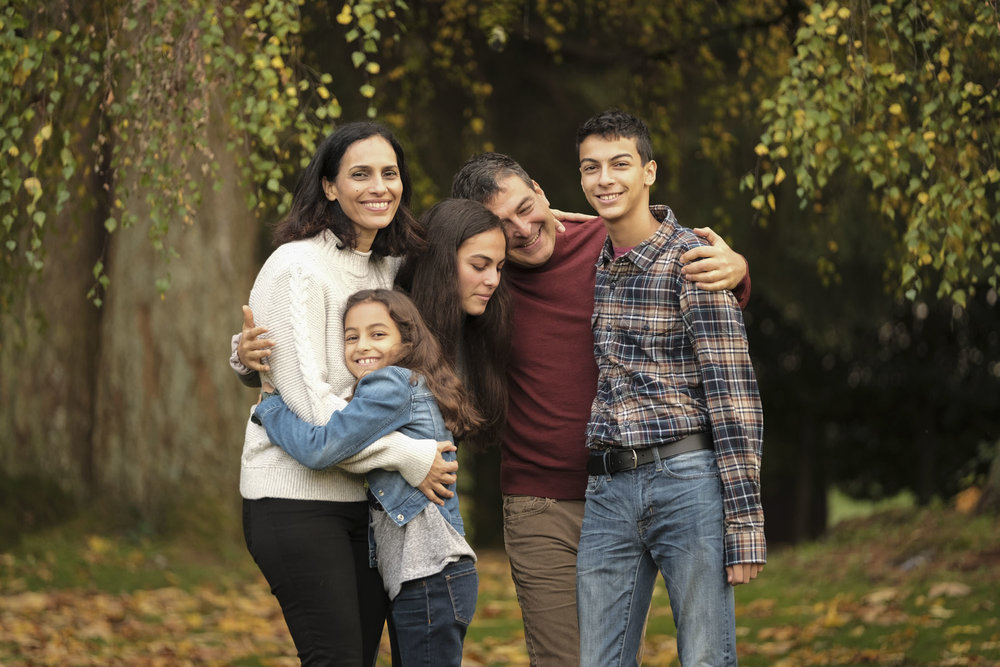 seattle family of five hugging in a park with fall leaves