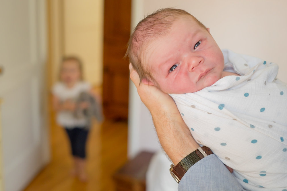 new baby looking at camera being held in hands with a toddler sister approaching in the background