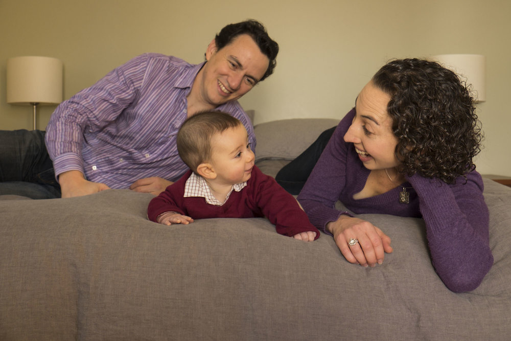 mom smiling at baby on bed with dad looking from behind