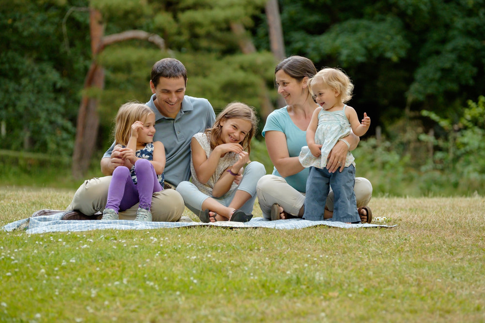 family of five sitting on a blanket in a green park laughing