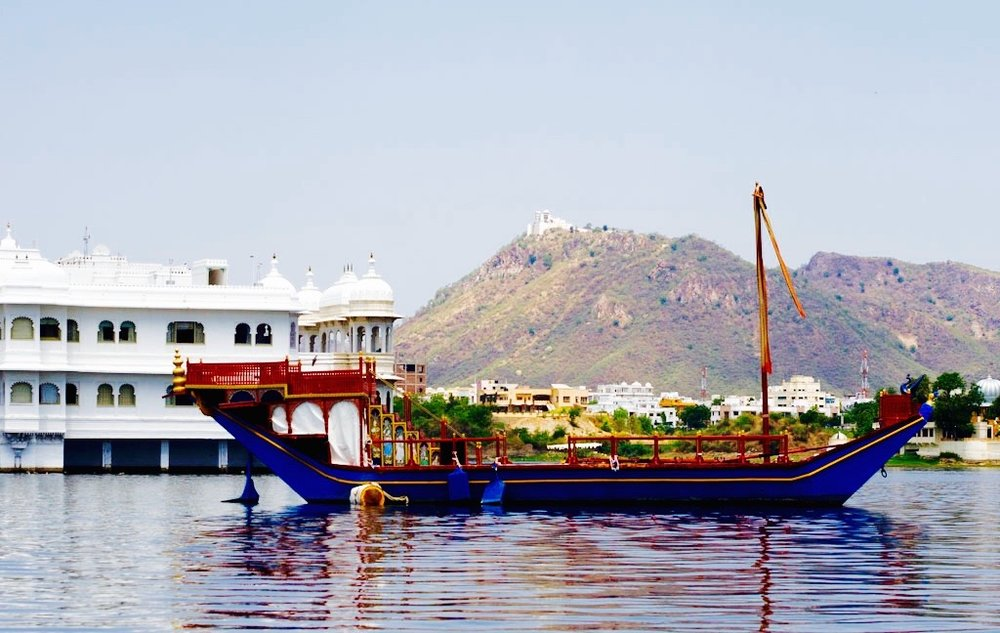 udaipur-rajasthan-india-lake-pichola-boat-ride-b-wooden-boat-near-the-jag-niwas-lake-palace-and-the-monsoon-palace-in-the-background.jpg