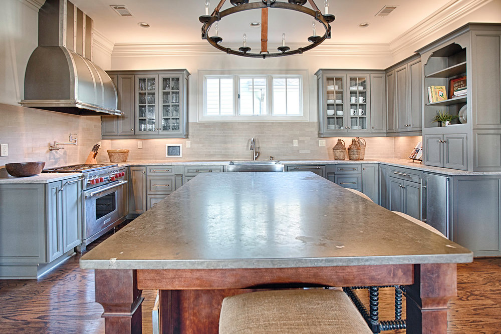 A large limestone island with contrasting quartzite countertops surrounding the kitchen