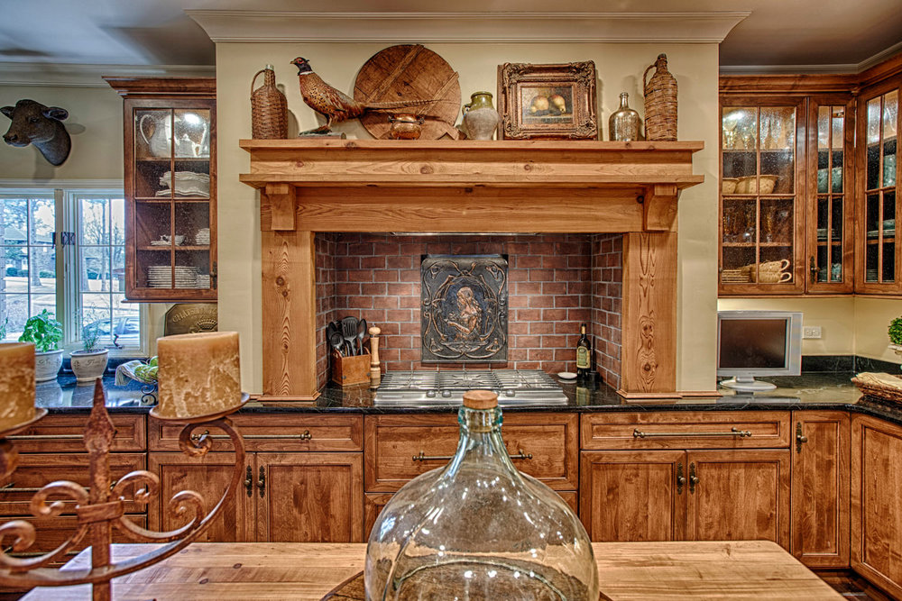 View a rustic French inspired kitchen design in a home located near the Indian Hills Country Club .