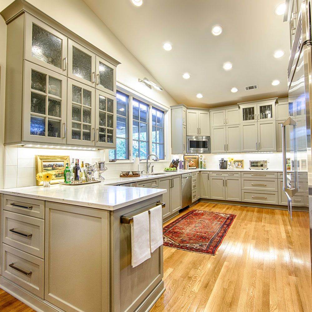 The cabinets have seeded glass doors, a tray storage cabinet, and wine storage.