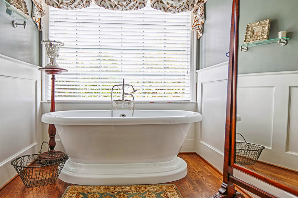 Shaker style beaded recessed wainscot panels, and hardwood floors are used within the tub area.