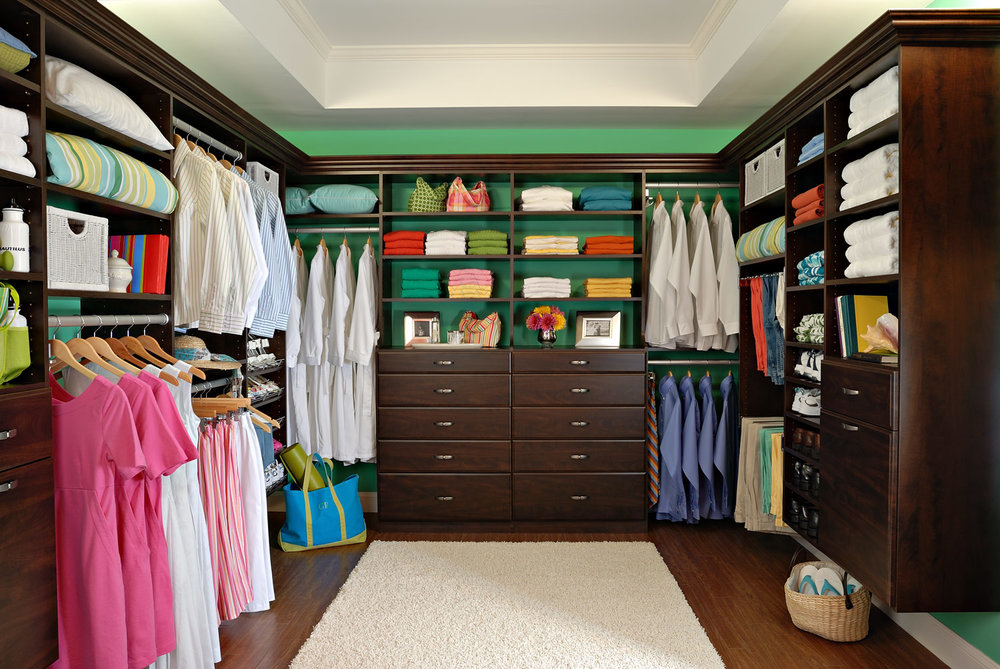 A dark brown custom designed walk in closet.
