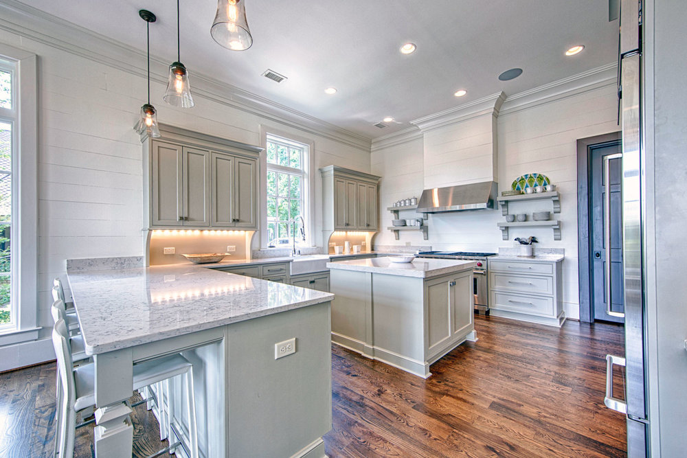 This traditional kitchen has open shelving to the sides of the professional Wolf range and shiplap walls.