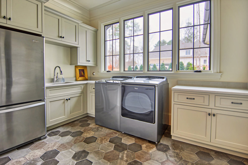 This custom laundry has appliances by Whirlpool, a sink and refrigerator.