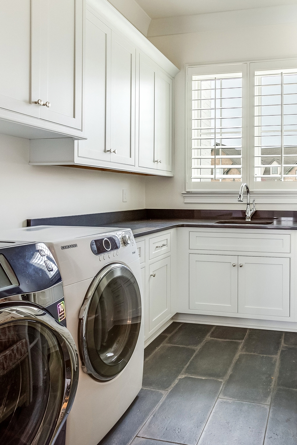 Custom laundry room design with stone floors.