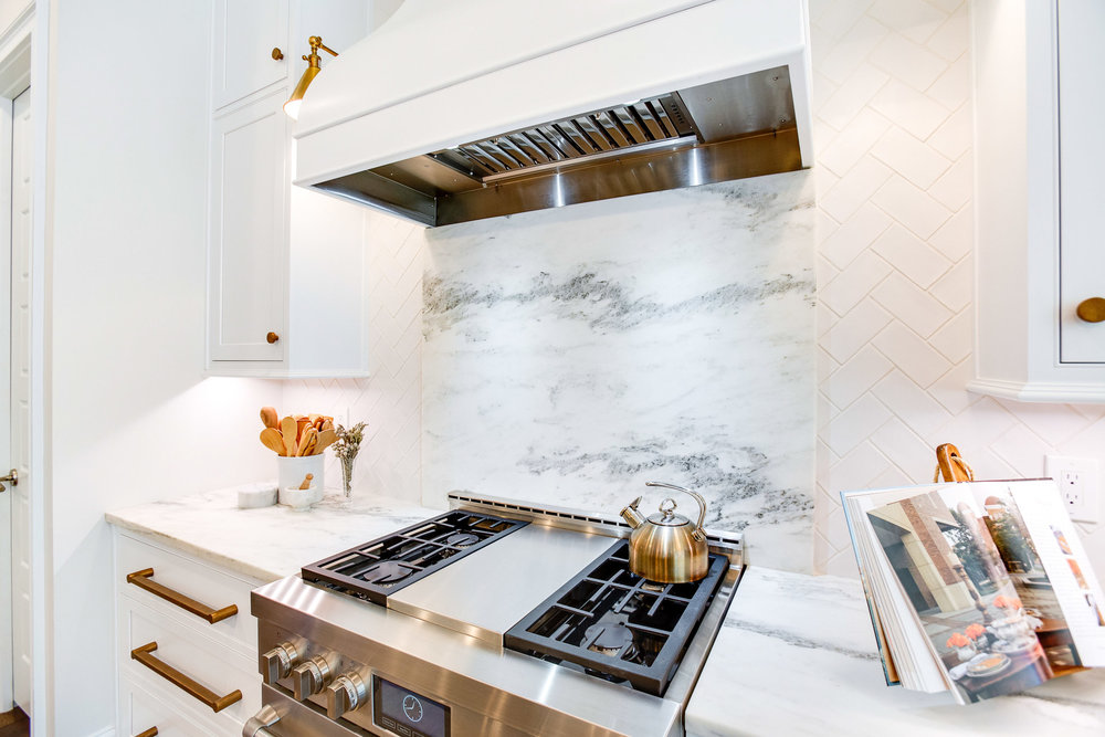 The backsplash behind the range is Montclair Danby marble. The tile is herringbone subway tile in mat crackle finish by Adex.