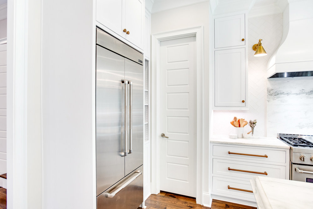 A Walk-in pantry is placed in close proximity to the kitchen island and Jenn-Air refridgerator.