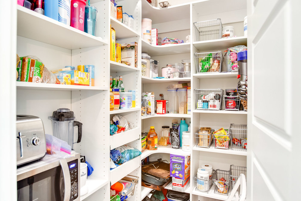 This functional walk-in pantry has adjustable shelving units and baskets.