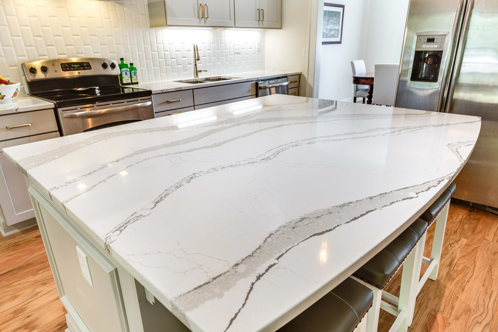 The Cambria Britannica quartz kitchen island countertop is arc shaped in the seating area.