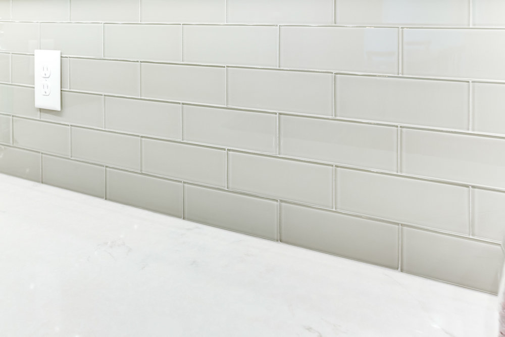 """The tile backsplash is Prima Tile clear glass 3"""" x 8"""" tile in Sterling."""