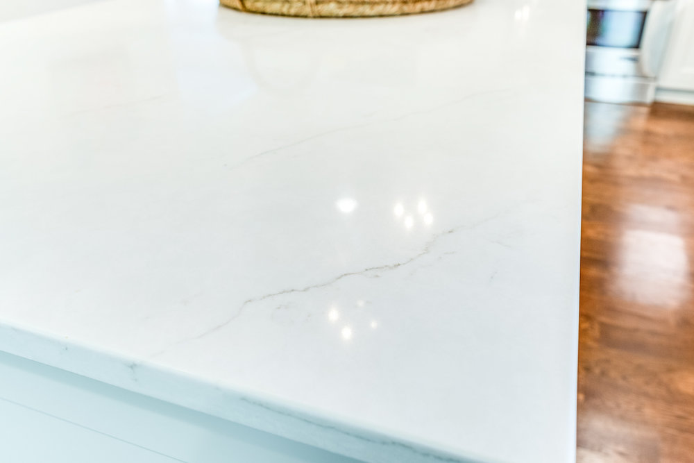 The kitchen island countertop is Dupont Zodiaq quartz in London Sky.