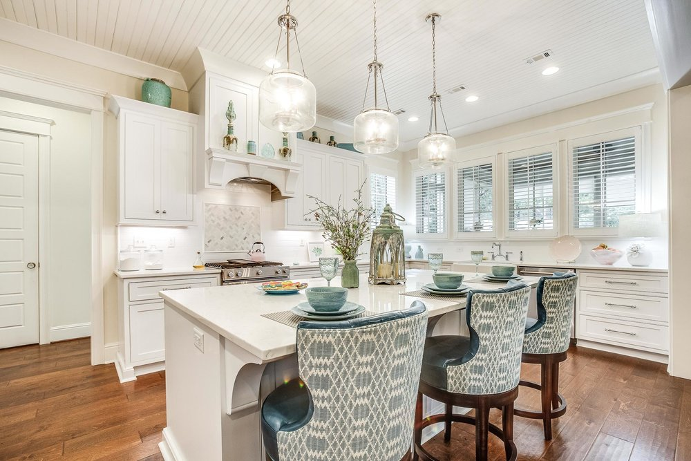 A kitchen island with a quartz countertop, large corbels, and seating for three.