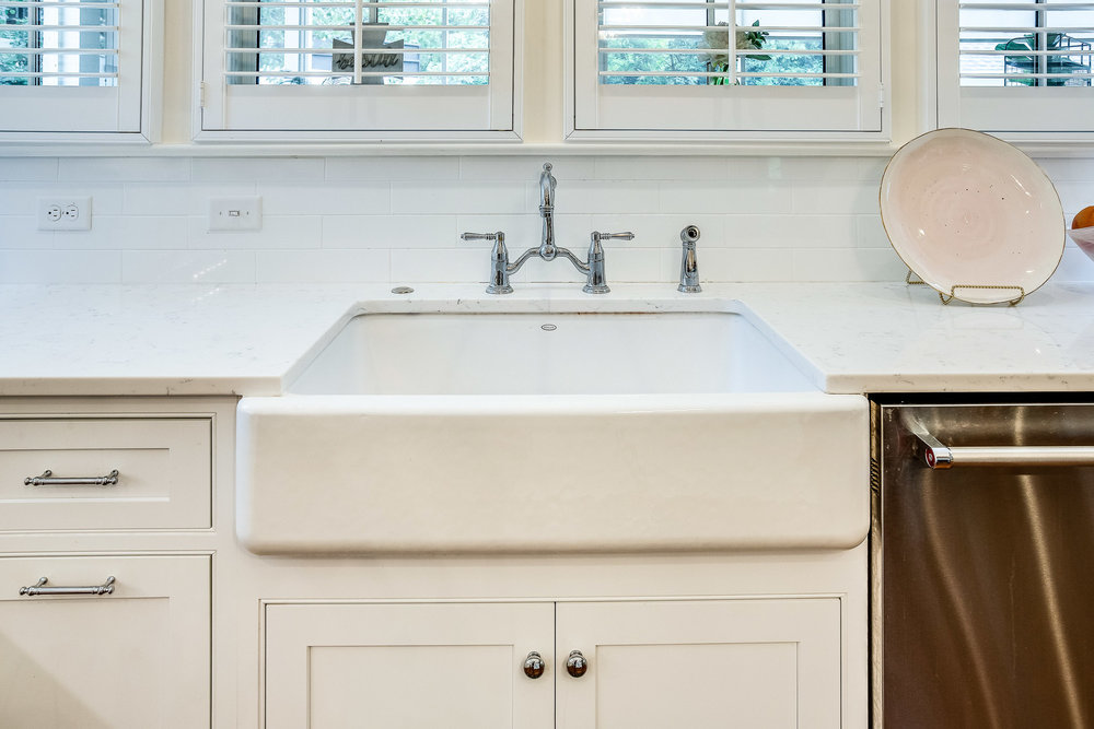 The farmhouse sink has a two-hole bridge kitchen faucet by Kohler.
