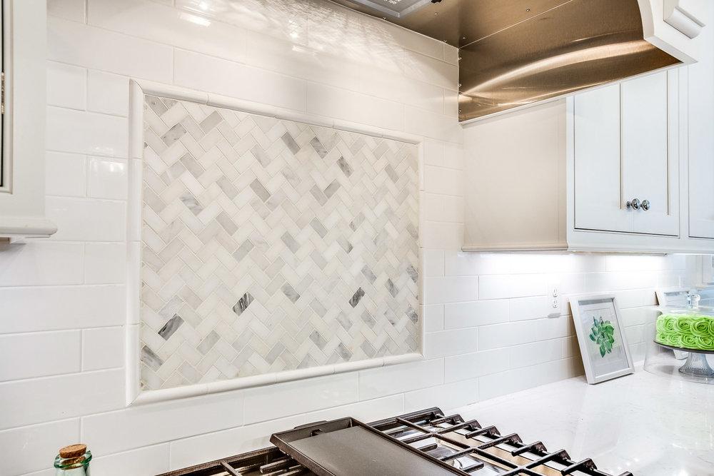 The backsplash tile behind the range is marble.