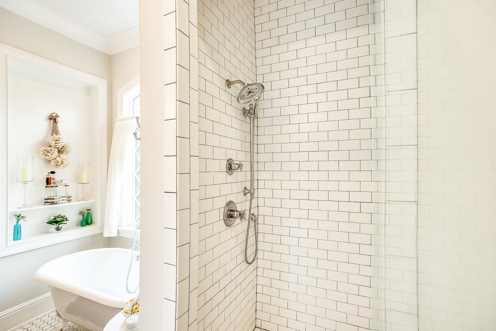 The tub filler with hand set and the shower fixtures are by Delta.