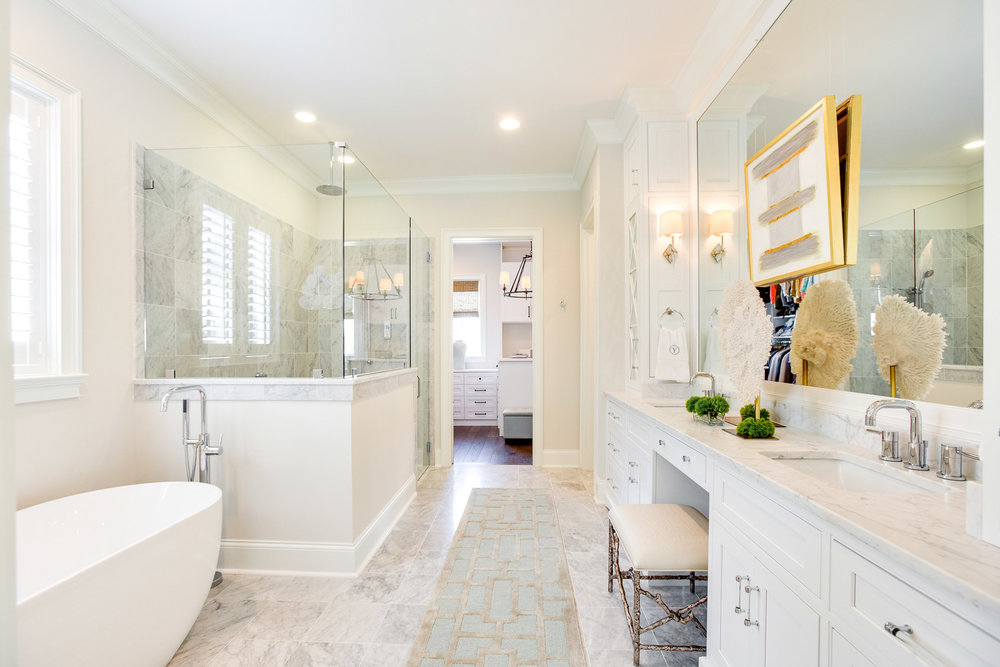 This master bathroom suite has a soaking tub, glass walled shower, a large vanity and Carerra Marble throughout.