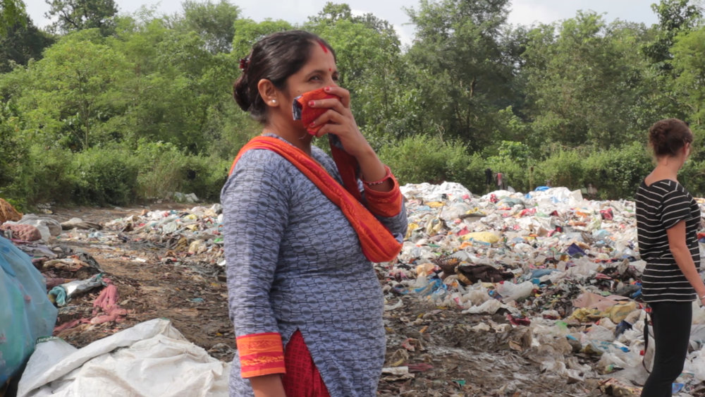 Local woman protecting herself from toxic fumes of dump site.
