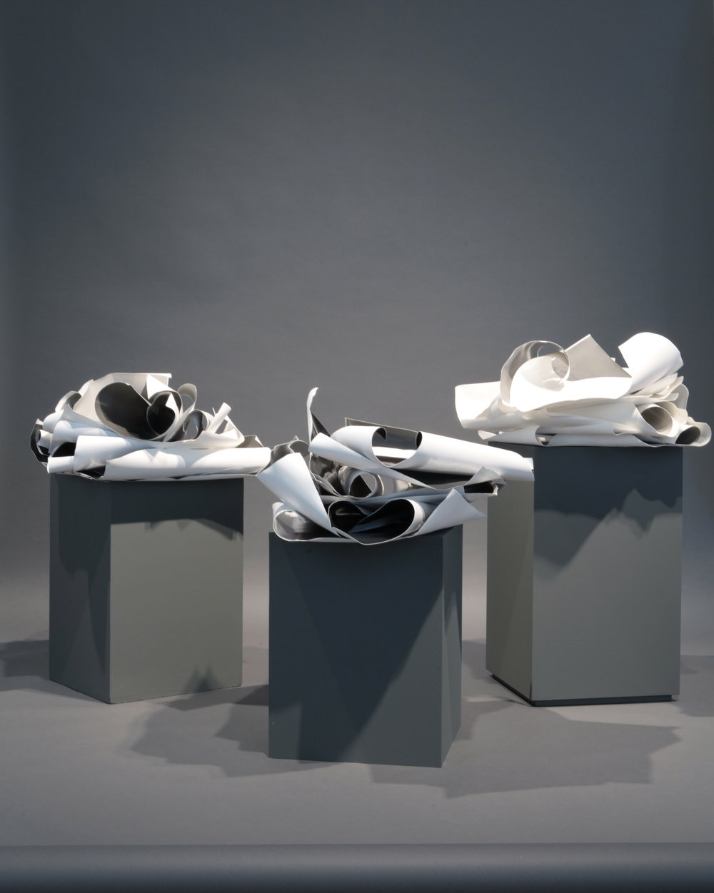 Posed (2015) Three stacks of silver gelatin prints on baryta paper, plinths of wood and neutral grey backdrop Installation, variable dimensions  Photo documentation: Adriana Alves/Kunsthall 3,14 Installation view at  Past Continuous in a Conditional Present,  Kunsthall 3,14, Bergen 2015