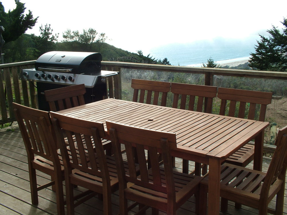 Dining table and barbecue on the deck with views of the ocean.