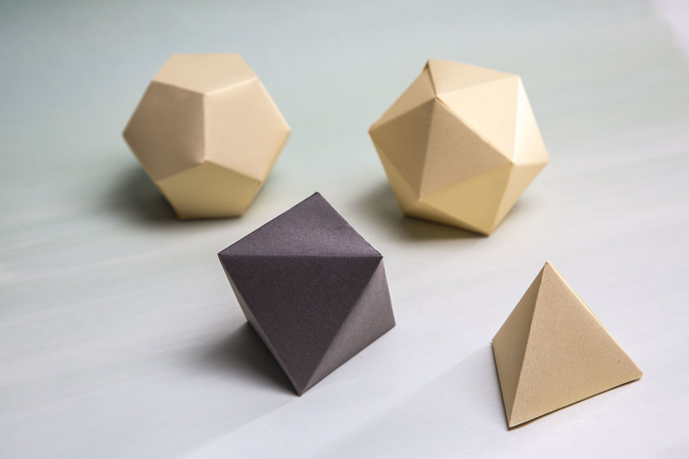 Geometric shapes made out of paper that serves as packaging for the pieces.