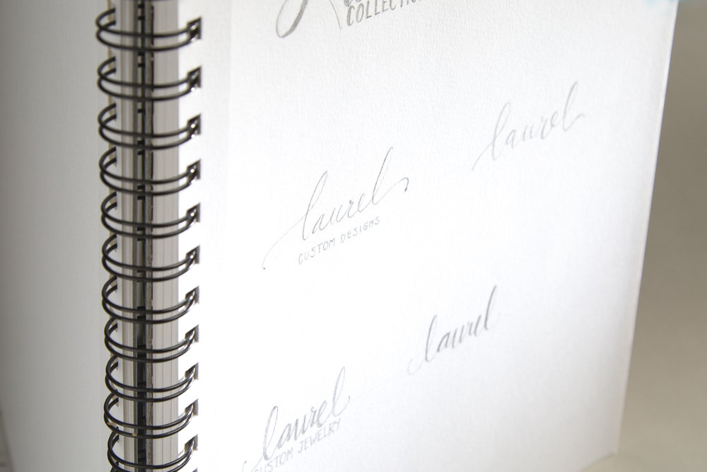Hand drawn pencil sketches of logo ideas in a notepad for Laurel Jewelry Design.