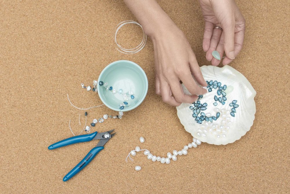 Hands creating jewelry, stringing beads together to show the process.