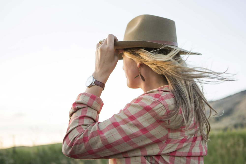 Woman standing in the wind with cowboy hat on.