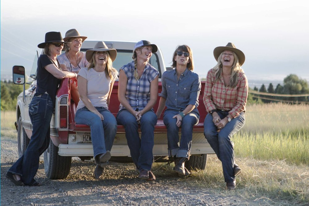 Group of women wearing cowboy hats laughing while sitting in a pickup truck.