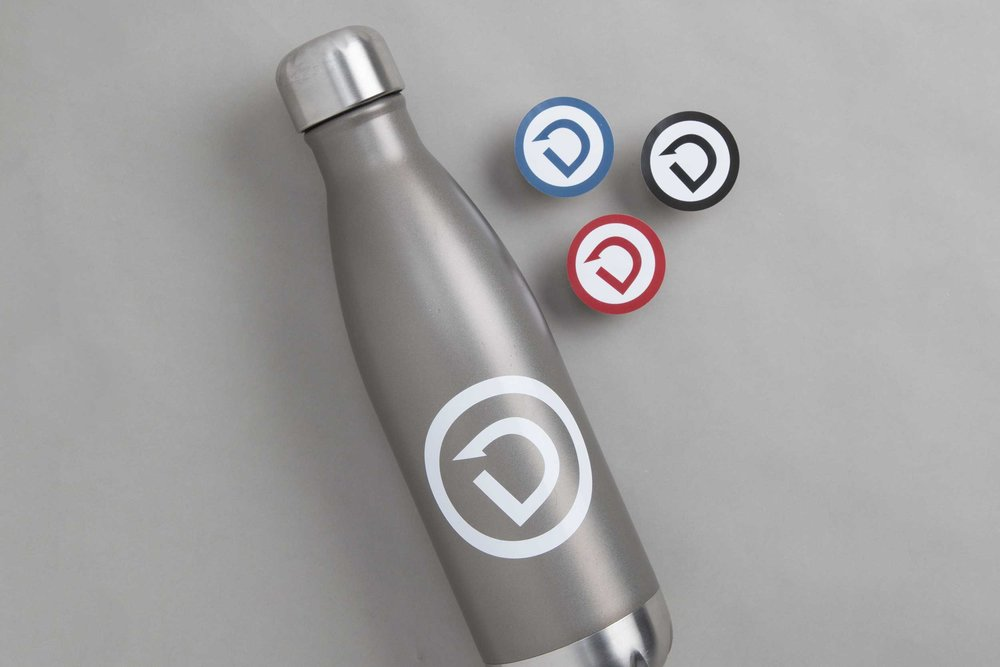 A water bottle and stickers with the Dare to Detour icon.