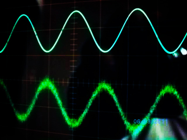 The top line is a smooth sine wave of alternating current (AC.) The bottom line is a sine wave corrupted with EMI.