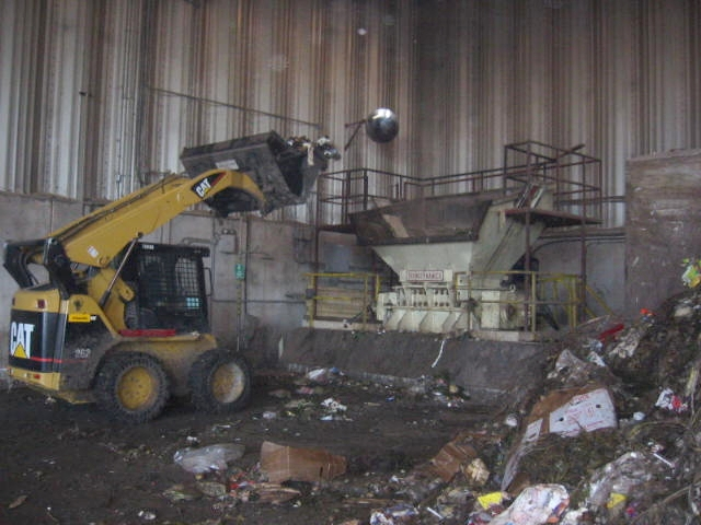 The organic material is then loaded into a coarse shear shredder for size reduction and then onto a conveyor belt for magnetic removal of ferrous metals, across a star screen for removal of oversize material and past an inspection station for removal of other contaminants. -