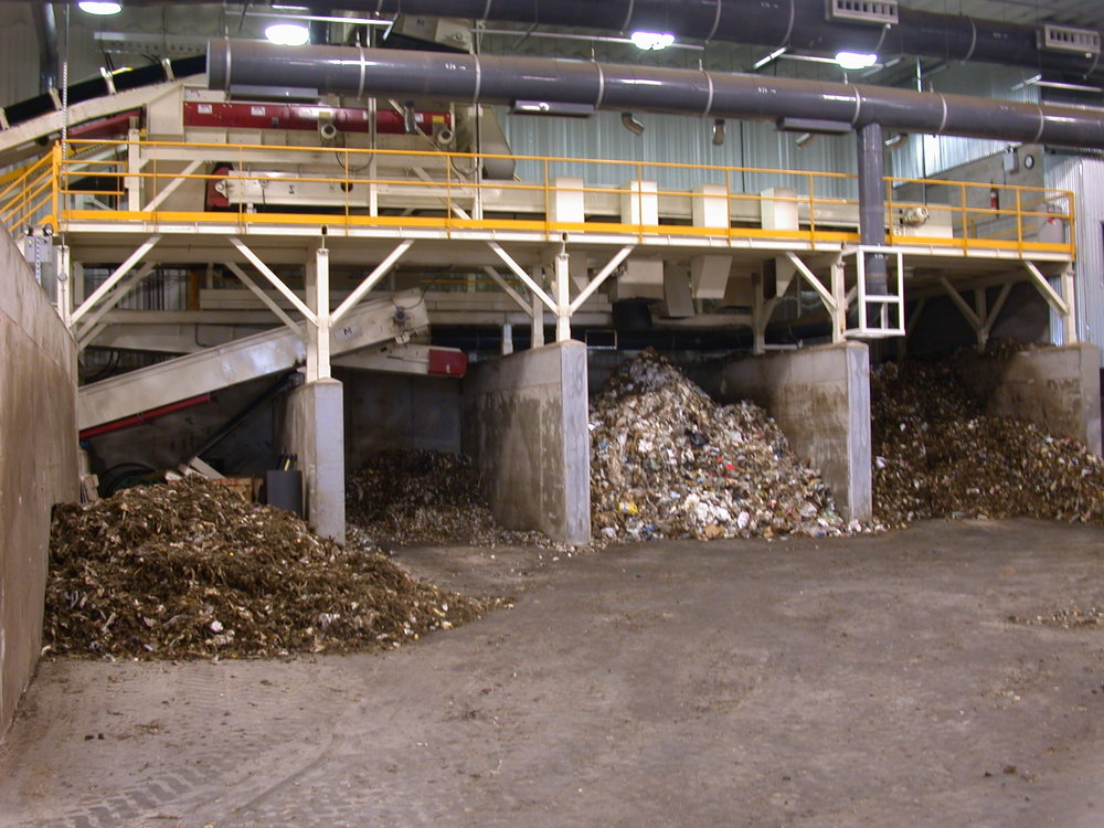 The feedstock is discharged into a holding bunker. Over 90%of the oversized materials removed by the star screen are cardboard, box board, or wood which are conveyed to a shredder. The shredded materials are discharged into a separate holding bunker for use as bulking materials.Additional bunkers for homogeneous organics and amendment materials are also provided in the Receiving Building. -