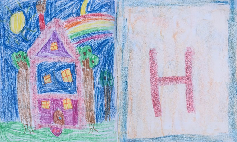 The letter 'H' is entered into a 1st grade lesson book, and illustrated with a house- notice the 'H' within the form of the house.