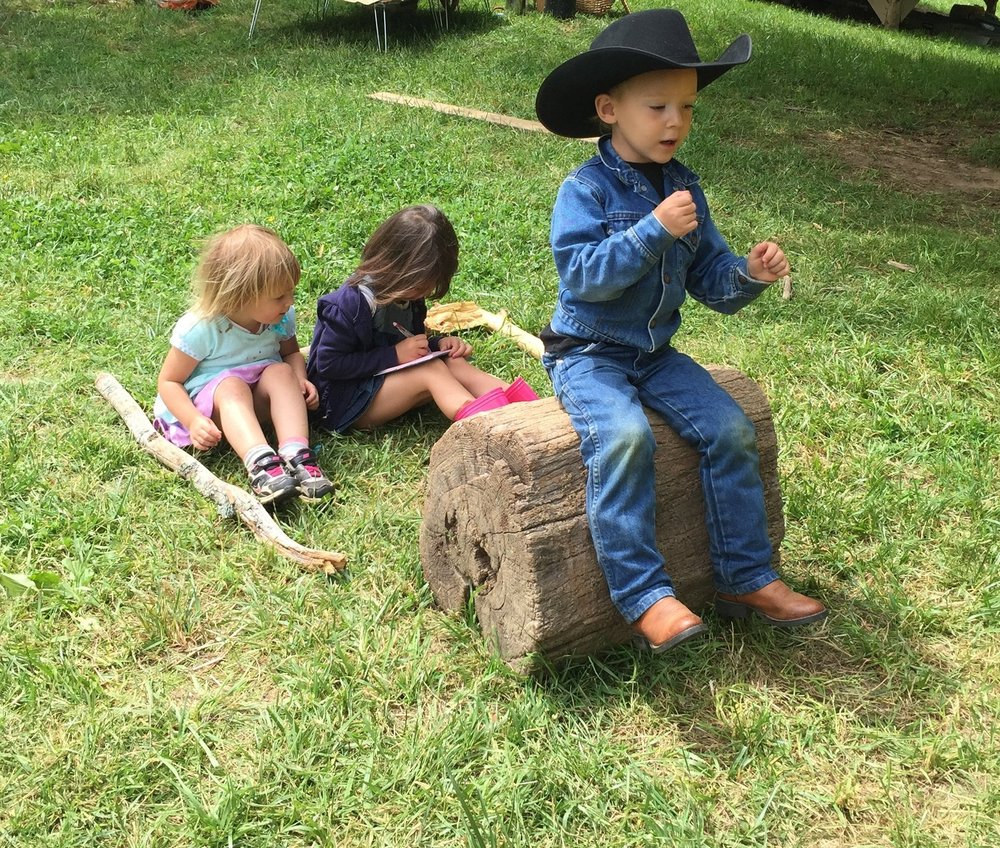 A log and sticks become a tractor in the imagination of the child.