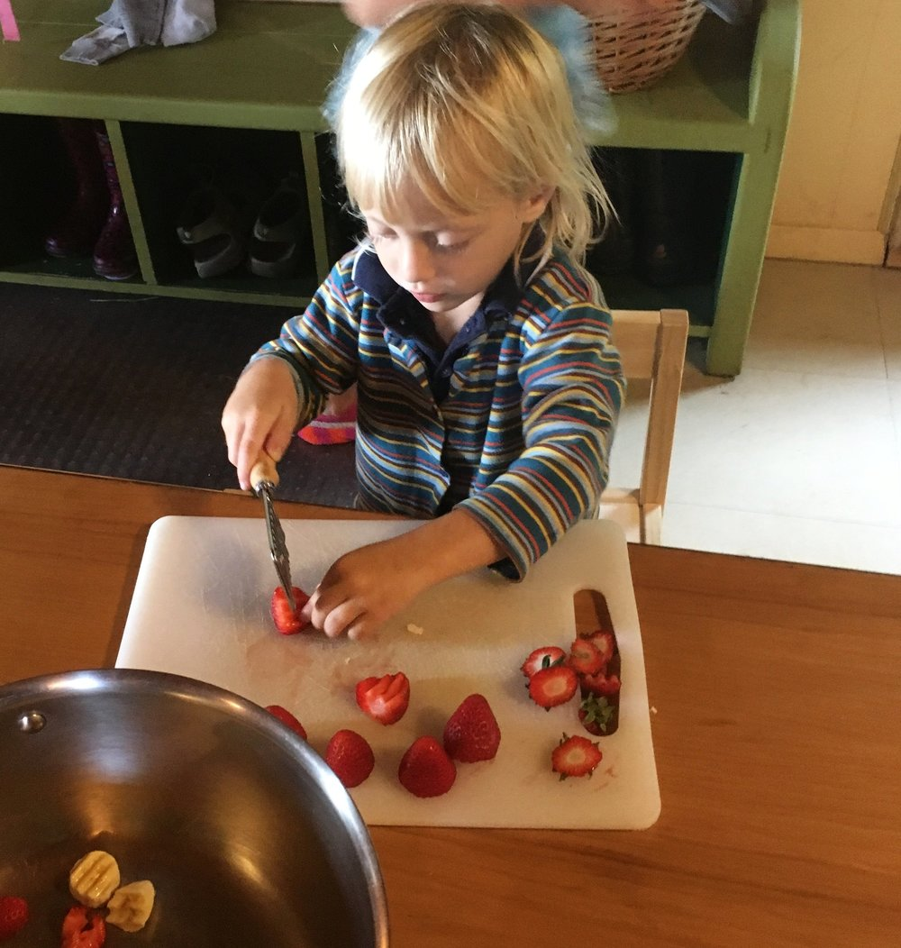 On 'Oatmeal Day', a child chops fresh strawberries from our gardens as a topping