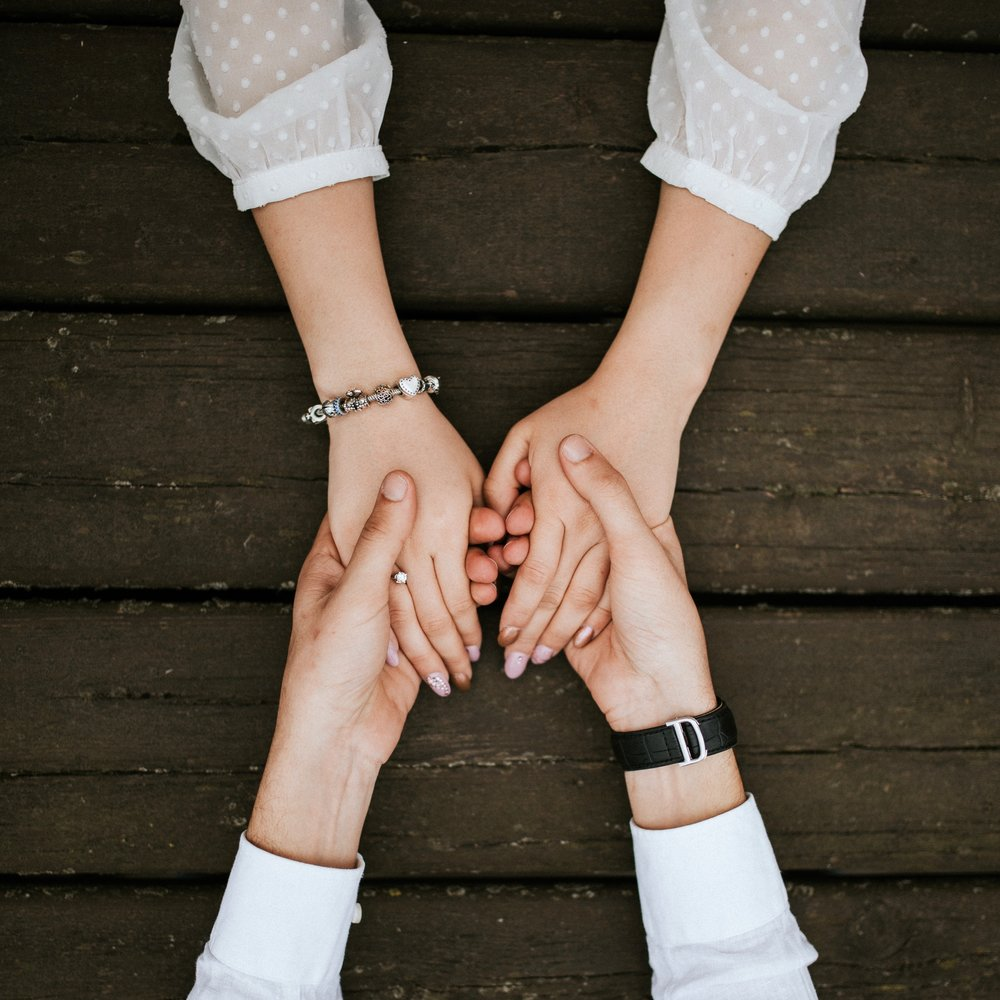 Serious Illness and Caregiver. Relationship Tool. Two Sets of Hands Holding Each Other on a Wooden Backdrop.