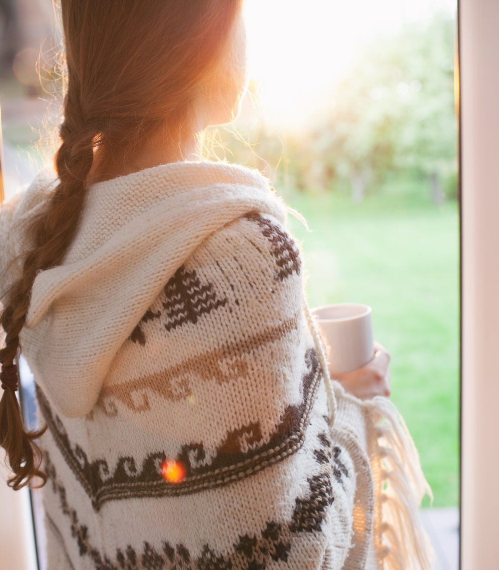 Serious Illness and Caregiver. Relationship Tool Empathy.  Person Wrapped in a White Shawl Looking out a windoww at the grass while sunlight streams in.