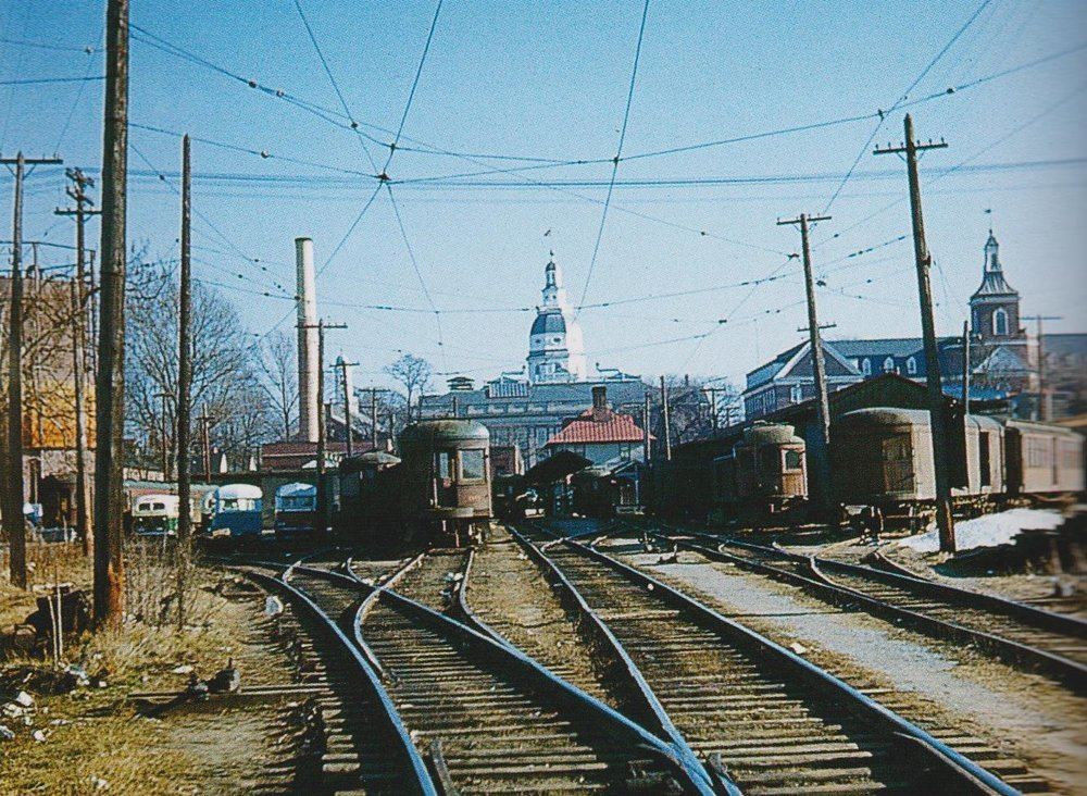 """Bladen Street terminal yard. To the left are B&A buses. Centered in the scene is the dome of the State Capital of Maryland. In front of the capital are two passenger cars, while to the right are, among other things, an ex-WB&A, ex-Long Island trailer, a freight trailer, and freight motor 18."" Annapolis, Maryland Date: Unknown. Source: Frank Watson Collection, ""Baltimore-Washington Trolleys, In Color"" by LeRoy O. King Jr."