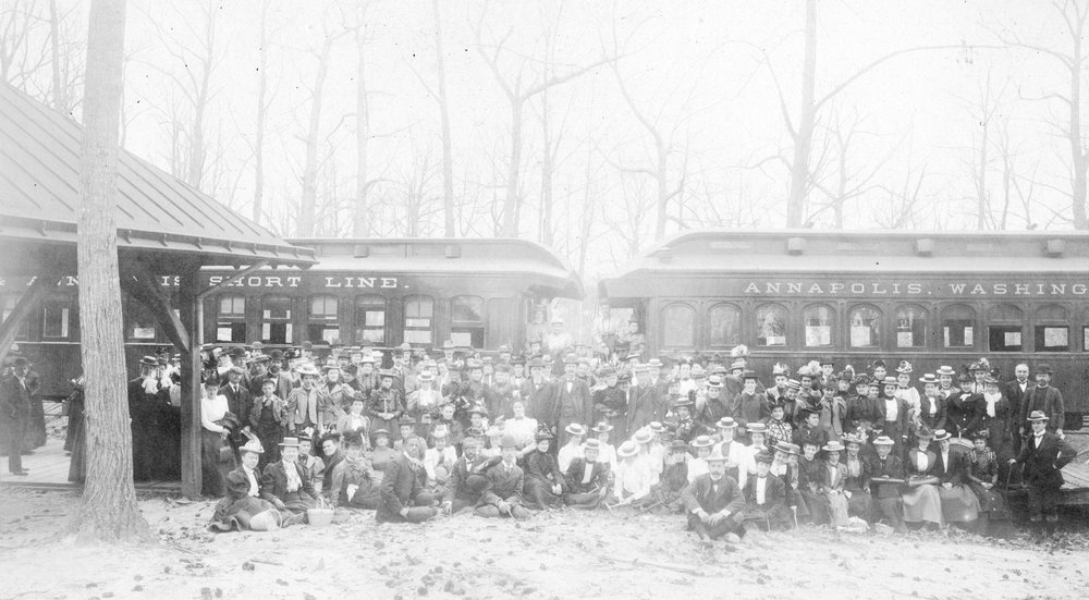 """Members of the Teachers Scientific Course are gathered in front of train cars on an excursion to Severn River, Maryland."" In the picture you can see a Baltimore & Annapolis Short Line Car & a Annapolis, Washington & Baltimore Railroad Car. Date: January 1, 1899. Source: JHU Sheridan Libraries/Gado/Getty Images."