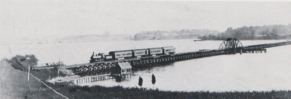 The Annapolis Short Line Steam Train crosses the Severn River Bridge towards Baltimore. Looking towards the South Shore. The Naval Academy can be seen in the top left corner. Annapolis, Maryland. Circa 1905. Source: Jacques Kelly Collection.