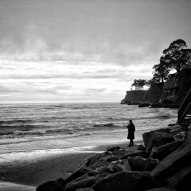 Black pants, shoes, trench coat and hat, smoking the doobage on the beach. Capitola, Ca